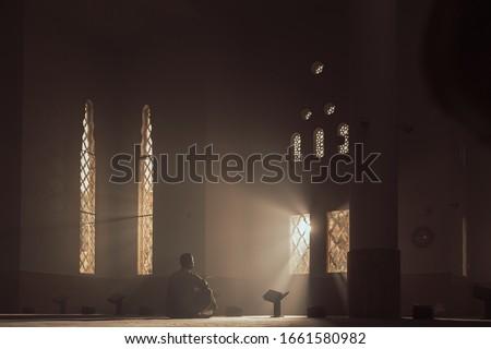 a man in a mosque reads the Qur'an an Arab in a white Kandur Arabic clothing outdoor Qur'an mosque night reading of the Qur'an Ramadan Islam religion Islam Royalty-Free Stock Photo #1661580982