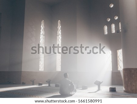 a man in a mosque reads the Qur'an an Arab in a white Kandur Arabic clothing outdoor Qur'an mosque night reading of the Qur'an Ramadan Islam religion Islam Royalty-Free Stock Photo #1661580991