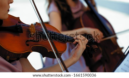 Musical Orchestra Of Female Musicians Plays On The Summer Terrace Outside, Hands Holding A Violin And Bow, Close Up Royalty-Free Stock Photo #1661590036