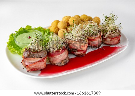 Beef minion in bacon with herbs in berry sauce with potatoes. Banquet festive dishes. Gourmet restaurant menu. White background.
