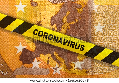 Travel ban and Coronavirus quarantine in Europe. Concept. 50 Euro banknote with EU map and yellow tape. Economy markets impacted by corona virus COVID-19 pandemic. Concept. Montage. Royalty-Free Stock Photo #1661620879