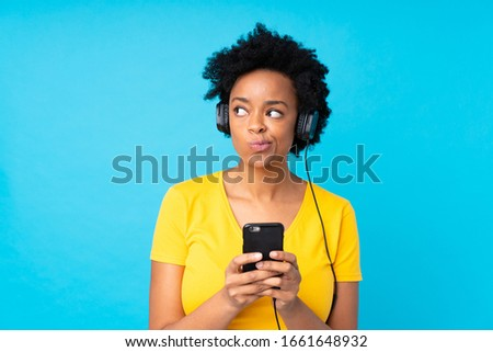 Young african american woman listening music with a mobile over isolated blue wall #1661648932