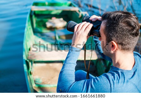 Man in the boat looking with field glasses on water surface.Male tourist using spyglasses on the lake #1661661880