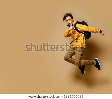 Young teen boy in comfortable clothing, sneakers, sunglasses and backpack jumping and feeling cool over yellow wall background. Stylish casual clothing for teenagers and freedom concept #1661702263