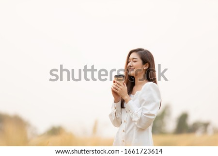 Young woman holding takeaway coffee cup standing outdoors at barley field land in the morning. #1661723614