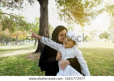 Arab mother kiss his son. Arabic parent shows love and affection to his boy child on Kandora. Arabian family on a park. Summer break holiday of Young Arab boy student pointing his fingers upward #1661773477