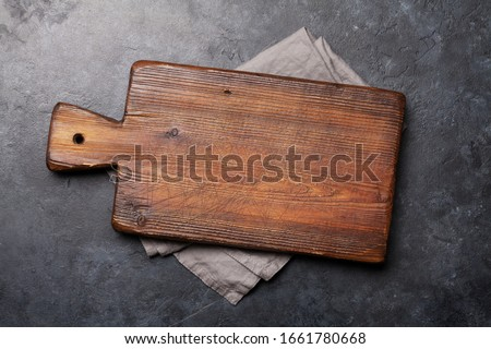Old cutting board over towel on stone kitchen table. Top view flat lay with copy space Royalty-Free Stock Photo #1661780668