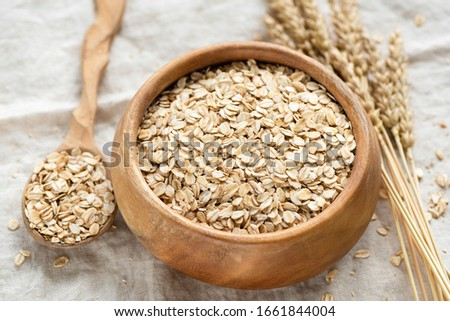Oat flakes, rolled oats in wooden bowl. Healthy food ingredients, low carb dry cereals for porridge, cookies, smoothies or granola #1661844004