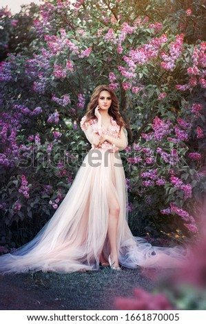 Beautiful young blonde hair woman in long pink dress with blossom lilac trees in spring garden #1661870005