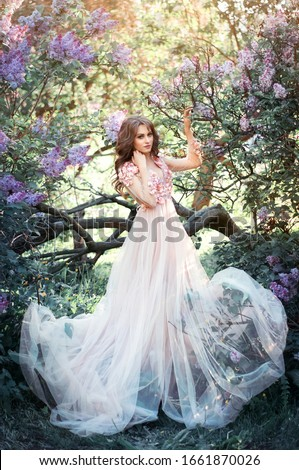 Beautiful young blonde hair woman in long pink dress with blossom lilac trees in spring garden #1661870026