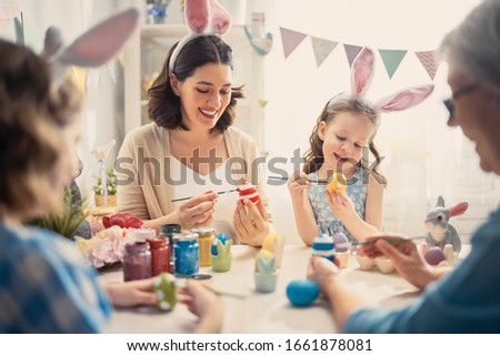 Mother, grandmother and daughters are painting eggs. Happy family are preparing for Easter. Cute little child girl wearing bunny ears.                                #1661878081
