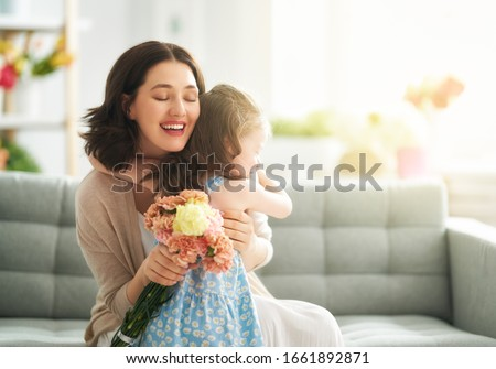 Happy mother's day! Child daughter congratulates mom and gives her flowers. Mum and girl smiling and hugging. Family holiday and togetherness. #1661892871