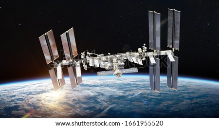 International space station on orbit of Earth planet. ISS. Dark background. Sun reflection. Elements of this image furnished by NASA Royalty-Free Stock Photo #1661955520