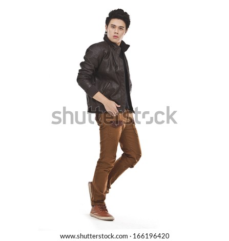 Full length young man standing with hands in pockets walking in studio #166196420
