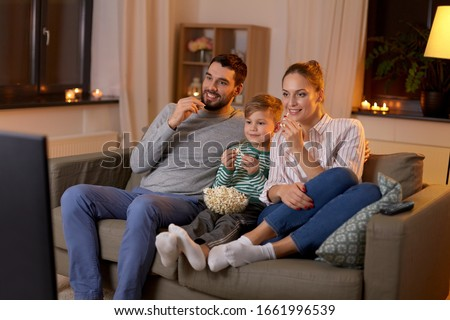 family, leisure and people concept - happy smiling father, mother and little son watching tv and eating popcorn at home at night #1661996539