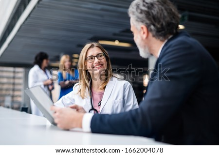 Doctor talking to a pharmaceutical sales representative. Royalty-Free Stock Photo #1662004078