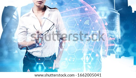 Unrecognizable businesswoman holding glasses over Moscow city background with double exposure of blurry futuristic digital interface. Concept of smart city and internet. Toned image #1662005041