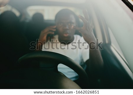 male young african american in car in white t-shirt #1662026851