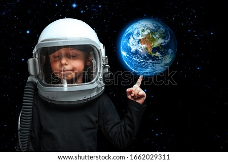 A small child imagines himself to be an astronaut in an astronaut's helmet. Elements of this image furnished by NASA #1662029311