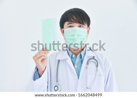 Asian male doctor wearing medical mask holding mask over white background.Health prevention concept. #1662048499