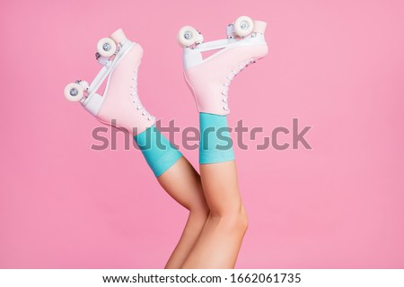 Cropped close-up profile side view of nice attractive lovely long legs wearing blue comfortable socks skates having fun time isolated over pink pastel color background