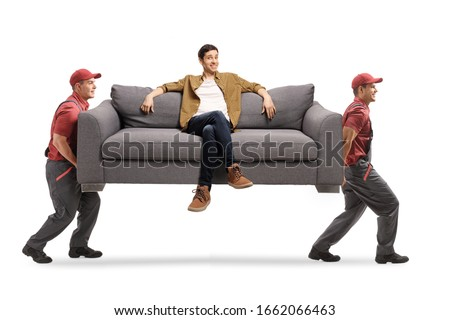 Two workers from a moving company carrying a sofa with a young man sitting isolated on white background