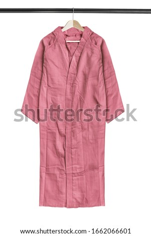 Pink oversized cotton kimono hanging on wooden clothes rack isolated over white #1662066601