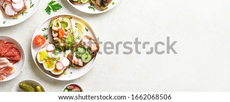 Sandwiches with meat, vegetables, seafood. Assortment open sandwiches on light stone background with free text space. Tasty healthy snack. Top view, flat lay. #1662068506