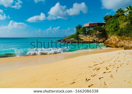 The Valley, Anguilla - January 10 2020:parasols on the beach of the Caribbean sea tropical island of Anguilla with palm trees #1662086338