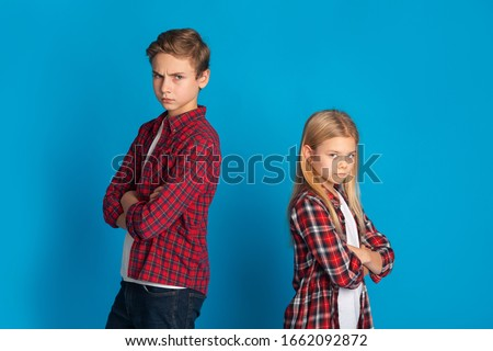 Siblings Conflicts. Offended Brother And Sister Standing Back To Back Not Talking To Each Other After Quarrel, Blue Studio Background With Copy Space
