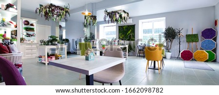 Tropical cafe in the city. Lamp are flowers decorated , picture with grass on wall, bright armchairs in cafe