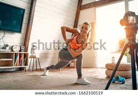 Athletic woman blogger in sportswear shoots video on camera as she does exercises at home in the living room. Sport and recreation concept. Healthy lifestyle. #1662100519