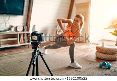 Athletic woman blogger in sportswear shoots video on camera as she does exercises at home in the living room. Sport and recreation concept. Healthy lifestyle. #1662100522