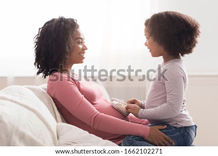 Little black girl playing with her expecting mom, putting small baby shoes on her pregnant belly, sitting on sofa at home, side view with free space #1662102271