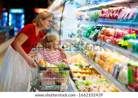 Shopping with kids. Mother and child buying fruit in supermarket. Mom and little boy buy fresh mango in grocery store. Family in shop. Parent and children in a mall choosing vegetables. Healthy food. #1662102439