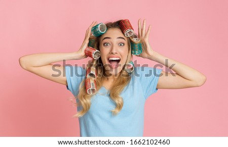 Very surprised woman with hair curlers holding her head with open mouth #1662102460