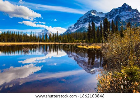 The mountains, forests and lake in the Rockies of Canada. Clouds reflected in the smooth water of the lake. Autumn trip to the Rockies of Canada. The concept of active, eco and photo tourism #1662103846