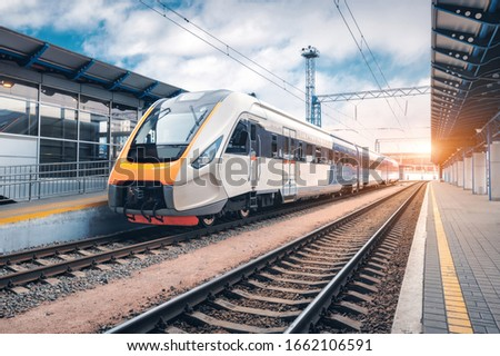 High speed train on the railway station at sunset. Industrial landscape with modern intercity passenger train on the railway platform and blue cloudy sky. Railroad in Europe. Commercial transportation #1662106591