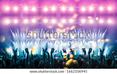 Concert hall crowded with colourful fans and lights Royalty-Free Stock Photo #1662106945