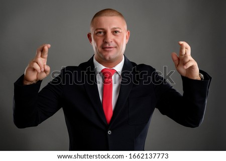 Cool businessman dressed in an elegant black suit and red tie showing double good luck isolated over gray background #1662137773