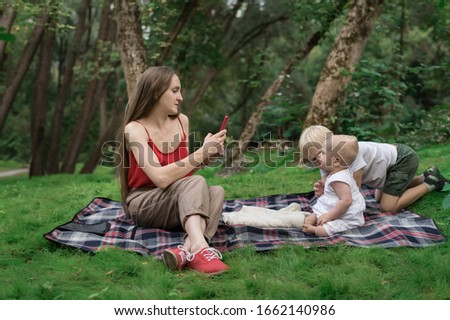 Mother with two children on picnic. Mom takes pictures of kids on phone