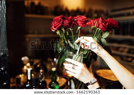 the girl is holding a refreshing cocktail with ice on the background of a large bouquet of red roses, a gift from a loved one and a drink prepared by the bartender in the restaurant #1662190363