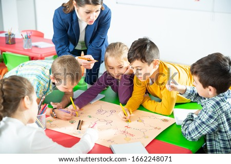 Teacher and collective of elementary age children draw together a board game