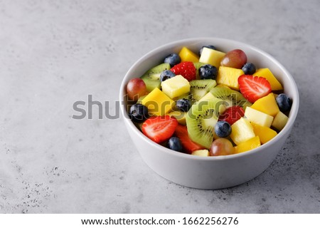 Fruit salad in bowl. Multi-colored ripe fruits and berries. Pineapple, mango, grape, strawberry, blueberry and kiwi #1662256276