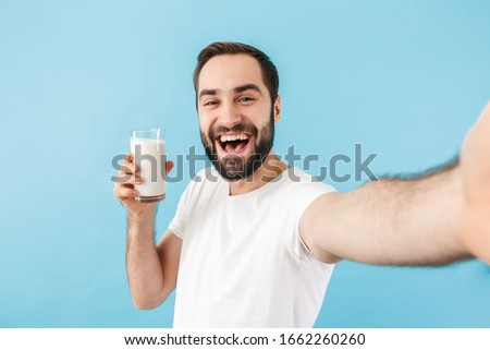 Portrait of a young cheerful excited bearded man wearing t-shirt standing isolated over blue background, showing glass of milk while taking a selfie