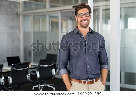Portrait of young businessman wearing eyeglasses and standing outside conference room. Portrait of happy business man wearing spectacles and looking at camera with copy space. Satisfied proud man. Royalty-Free Stock Photo #1662291385