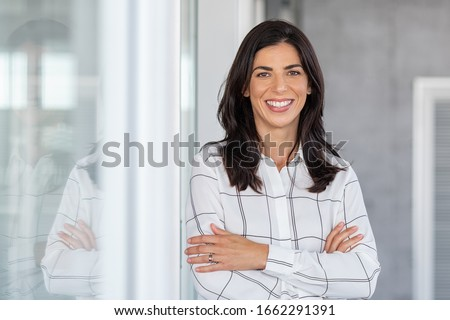 Portrait of middle aged businesswoman in modern office looking at camera. Confident business woman with arms crossed standing while leaning against glass wall. Proud woman smiling in with copy space. #1662291391