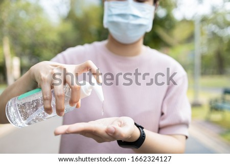 Asian people using alcohol antiseptic gel and wearing prevention mask,prevent against infection of Covid-19 outbreak,woman washing hands with hand sanitizer to avoid contaminating with Corona virus   Royalty-Free Stock Photo #1662324127