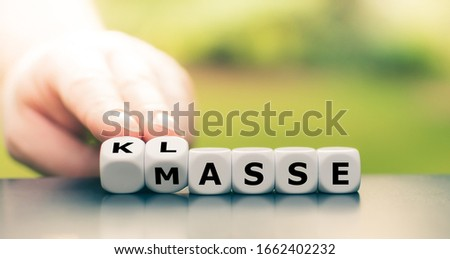 """Quality instead of quantity. Hand turns dice and changes the German word """"Masse"""" (""""quantity"""") to """"Klasse"""" (""""quality""""). #1662402232"""