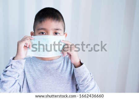 Portrait Asian kid wearing medical mask.A boy wearing mouth mask against air smog pollution. Concept of corona virus quarantine or covid-19.Protection against virus and infection control concept. #1662436660